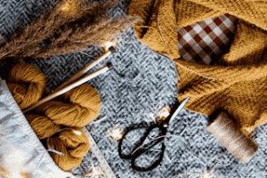 Outils pour tricoter, aiguilles et ciseaux pour faire un cadeau maison comme un plaid, un bonnet pour faire de votre noël une soirée exceptionnel et eco-responsable
