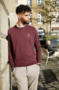 Modèle homme portant un pull bordeaux en coton bio à col rond de la marque Coton Vert parfait pour offrir à un homme ou une femme pour un noël ecologique, la marque étant mixte