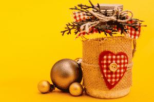 Photo d'un bocal en verre décoré avec des éléments comme du tissu, de la ficelle, des boutons et branches sur fond jaune afin d'emballer ses cadeaux de manière réutilisable