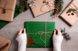 Photo avec divers cadeaux emballés avec du papier kraft et décorés avec de la ficelle et des branches c'est une des manières d'emballer des cadeaux de manière éco-responsable