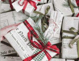 Photo de plusieurs cadeaux emballés avec du papier journal et des rubans de diverses couleurs pour emballer ses cadeaux éco-responsable